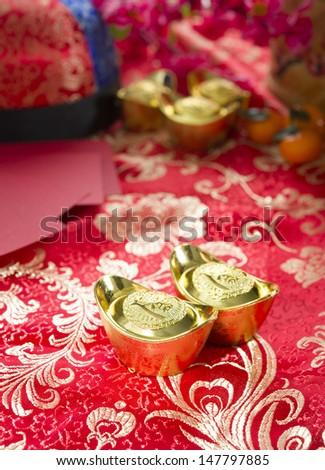 Chinese gold ingot with setups on background - stock photo