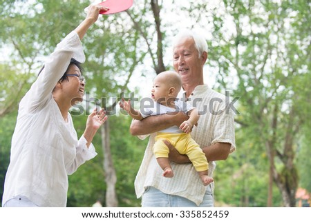 chinese grandfather and grandmother playing with baby grandson at outdoor - stock photo