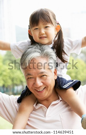 Chinese Grandfather Giving Granddaughter Ride On Shoulders In Park - stock photo