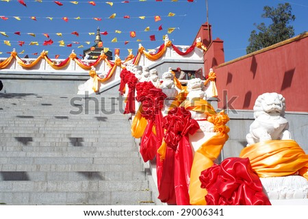 Chinese guardian lions in front of the temple are decorated with colored ribbons during religious activities