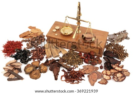 Chinese herb ingredients used in traditional herbal medicine with old brass scales over white background. - stock photo