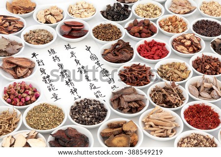 Chinese herbal medicine ingredients with calligraphy on rice paper. Translation reads as chinese herbal medicine as increasing the bodys ability to maintain body and spirit health and balance energy. - stock photo