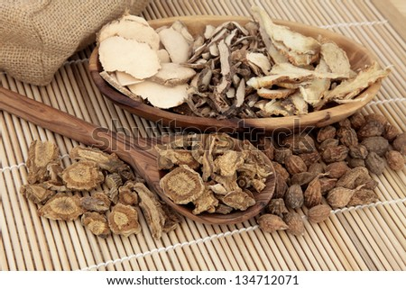 Chinese herbal medicine selection in a wooden spoon, bowl and loose over bamboo mat. - stock photo
