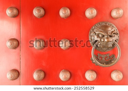 Chinese lion face door knob on the red gate of buddhist temple in Singapore.. - stock photo
