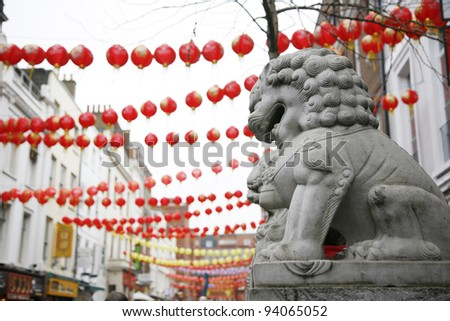 Chinese lion statue and red lanterns on Chinese New Year - stock photo