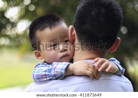 Chinese little boy hugging his father. The boy looks thoughtfully to one side. Selective focus. - stock photo