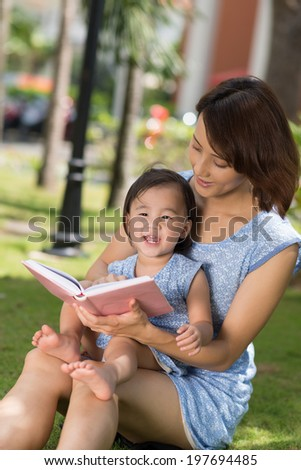 Chinese little girl and her mother reading a book in the park - stock photo