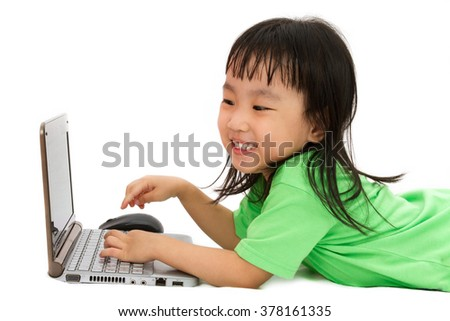 Chinese little girl lying down with laptop in plain white isolated background. - stock photo