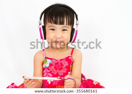 Chinese little girl on headphones holding mobile phone in plain isolated white background. - stock photo
