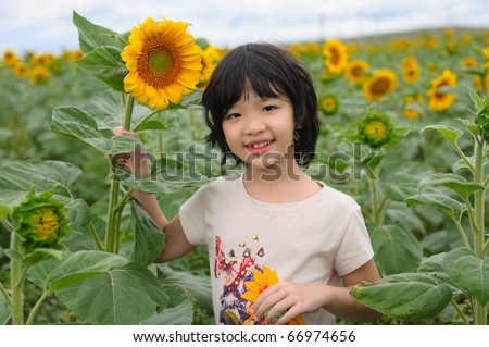 Chinese little kid smiling in the sunflower field - stock photo