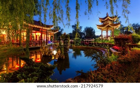 Chinese looking restaurant in front of pond - stock photo
