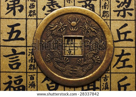 Chinese lucky coin on hieroglyphic background - stock photo