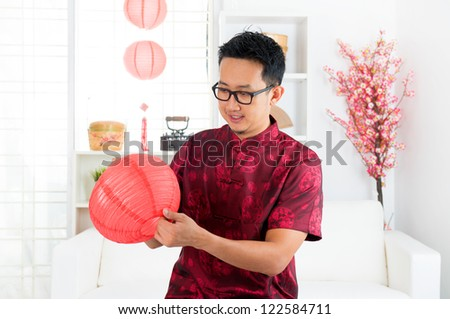 Chinese man decorating house for Chinese new year - stock photo