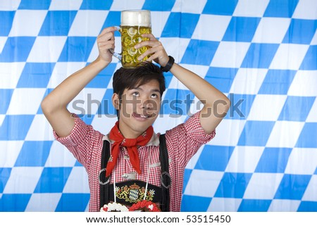 Chinese man dressed with Bavarian Lederhose holds an full Oktoberfest beer stein on his head and looks up. In background is the Bavarian flag visible. - stock photo