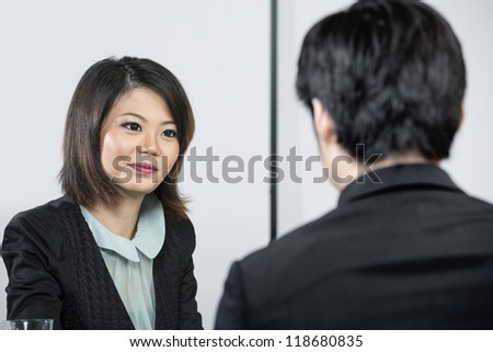 Chinese man having an interview with female manager. - stock photo