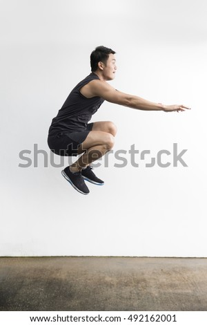Chinese man jumping while doing sport. Action and healthy lifestyle concept.