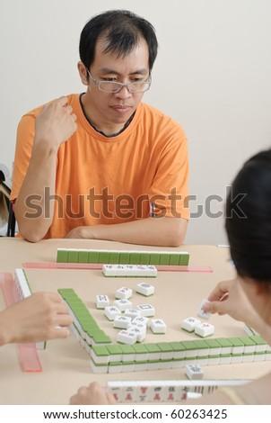 Chinese man play Mahjong, traditional China gamble. - stock photo