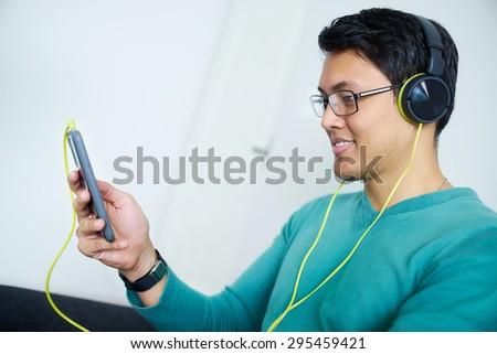 Chinese man relaxes on sofa and watches podcast on mobile phone, listening with green big earphones. Copy space - stock photo
