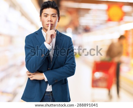 chinese man silence gesture - stock photo