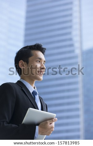 Chinese man with a tablet computer. Asian business man holding a digital tablet computer, standing in front of a skyscraper. - stock photo