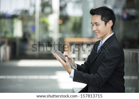 Chinese man with a tablet computer. Asian business man using digital tablet computer outside.