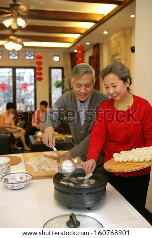 Chinese mature couple making chinese dumpling on New year's Eve - stock photo