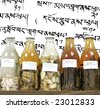 chinese medicine herbs and concoctions in large bottles on tibetan writing background - stock photo