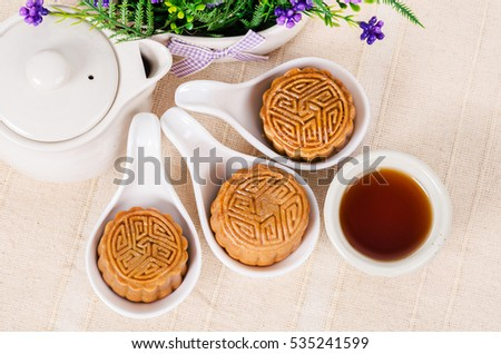 Chinese mid autumn festival foods. Traditional mooncakes on table setting with teapot.