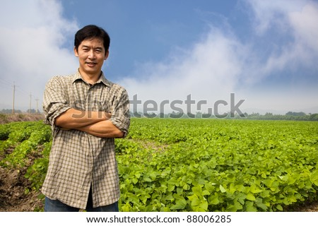 chinese middle aged  farmer and his farm - stock photo