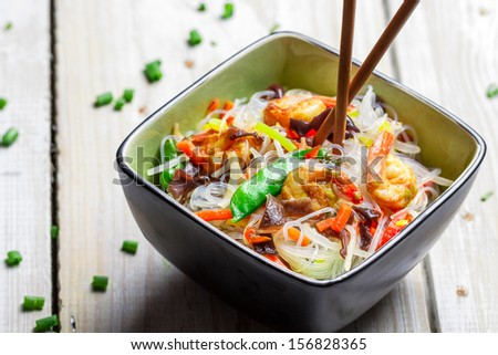 Chinese mix vegetables and rice noodles on old wooden table - stock photo