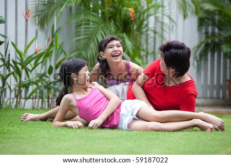 Chinese mom having fun with her daughters in the garden - stock photo