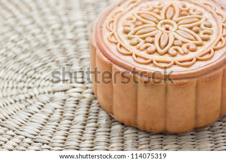 Chinese moon cake on a bamboo plate.