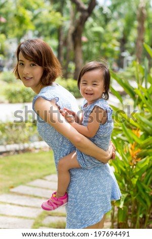 Chinese mother and daughter in the same dresses playing in the park - stock photo