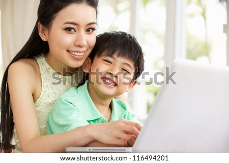 Chinese Mother And Son Sitting At Desk Using Laptop At Home - stock photo