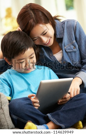 Chinese Mother And Son Using Tablet Computer Whilst Sitting On Sofa At Home - stock photo