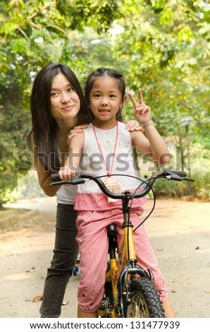 chinese mother having good time on bicycle with her daughter outdoor, peace sign - stock photo