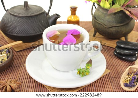 Chinese natural medicine with a cup of tea and flower petals and stones - stock photo