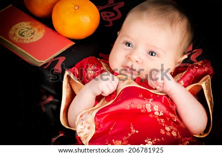 Chinese New Year baby with orange, red packets with red chinese outfit