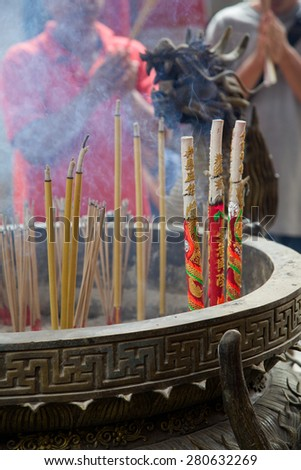 Chinese New Year celebrations in Phuket, Thailand. A family light incense at a temple on the first day of the 3-day vacation. - stock photo