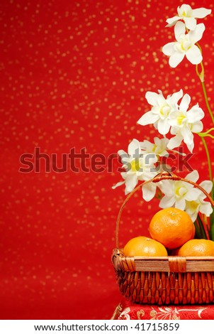 Chinese new year decoration--A basket of oranges with daffodil on a festive background. - stock photo