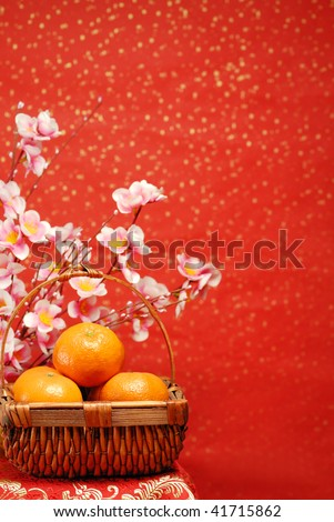 Chinese new year decoration--A basket of oranges with plum flower on a festive background. - stock photo