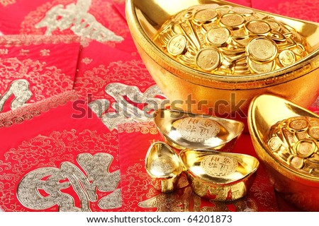 Chinese New Year Decoration--Gold ingots on red envelope. - stock photo