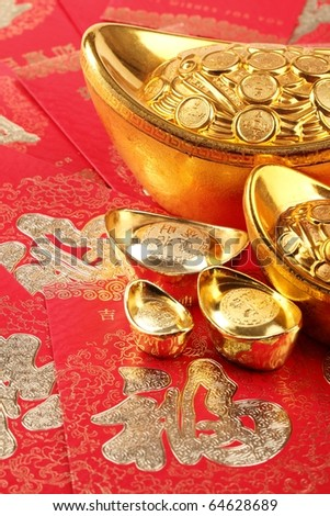 Chinese New Year Decoration--Gold ingots on red envelope. - stock photo