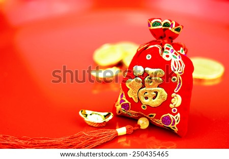 "Chinese new year decoration: red felt fabric bag or ang pow with word "" prosperous "" and golden ingots on red glossy floor - stock photo"