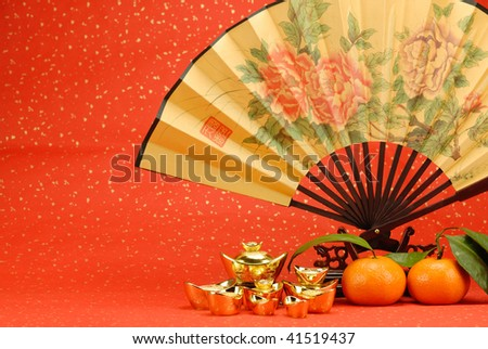 Chinese new year decoration--Traditional fan with gold ingot and orange on festive background. - stock photo