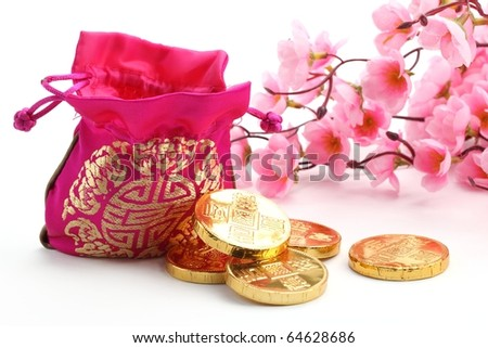 Chinese New Year Decoration--Traditional money bag,gold coin and pink plum blossom. - stock photo