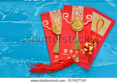 Chinese New Year Decorations  red envelope and Traditional chinese knots ornament  meaning safe trip wherever you go. (Foreign text means spring season greeting) - stock photo