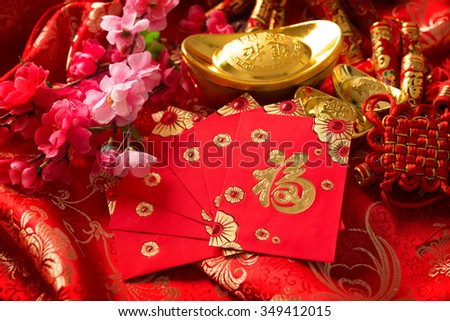 "Chinese new year festival decorations, ang pow or red packet and gold ingots. Chinese character means ""good fortune"", not logo and copyright. - stock photo"