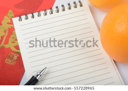 Chinese new year festival decorations. Oranges, notebook, and pen isolated over white background. Golden Chinese letter means luck.