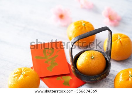 Chinese New Year - Mandarin orange and red packet (Foreign text means spring season) on white painted wood table - stock photo